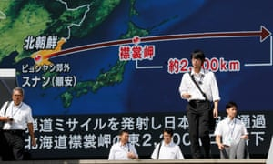 Pedestrians in Tokyo walk under a large-scale monitor displaying the flying course of a North Korean ballistic missile flying over Japan on Friday.