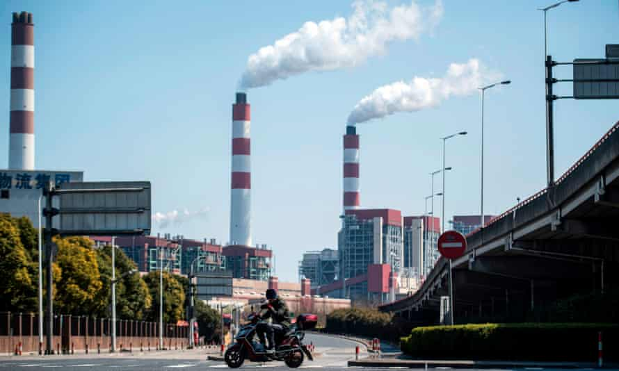 A man rides his scooter near the a coal power plant in Shanghai.