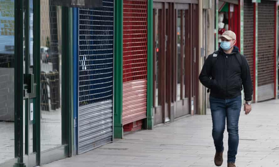 A man wearing a surgical face mask walks past closed shops on March 31, 2020 in Cardiff, United Kingdom.