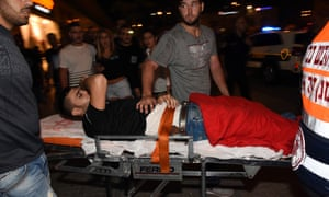 An injured man is taken away on a stretcher from the scene of an attack at the central bus station in Beersheba, Israel.