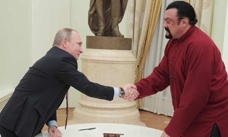 Vladimir Putin presenting Steven Seagal with a Russian passport.