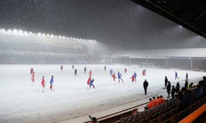 A view of play as snow covers the pitch.