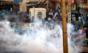 Smoke fills the air on a street in Khartoum after security forces use tear gas to disperse anti-government protesters