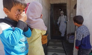Syrian children watch a member of the White Helmets disinfecting a building inhabited by displaced families in the rebel-held town of Binnish in Idlib province.
