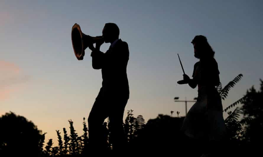 A swing band performs outside against a sunset