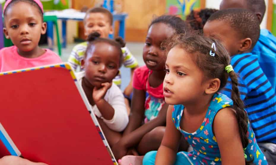 Nursery school children in South Africa are taught by a volunteer teacher.