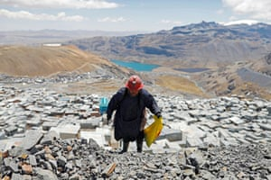 Chura strikes rocks that were discarded from a mine as she searches for gold