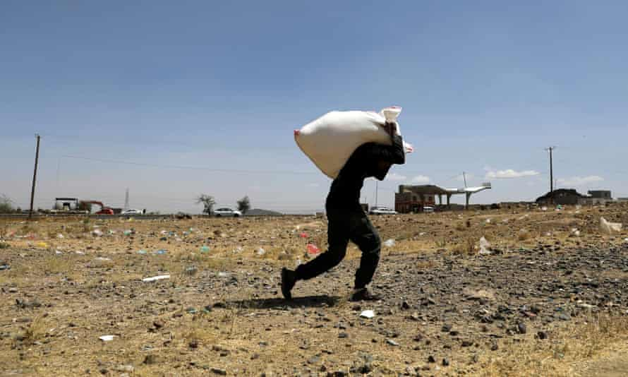 A man carries a sack of wheat flour from the Mona Relief charity at a camp for internally displaced people on the outskirts of Sanaa, Yemen, March 2021
