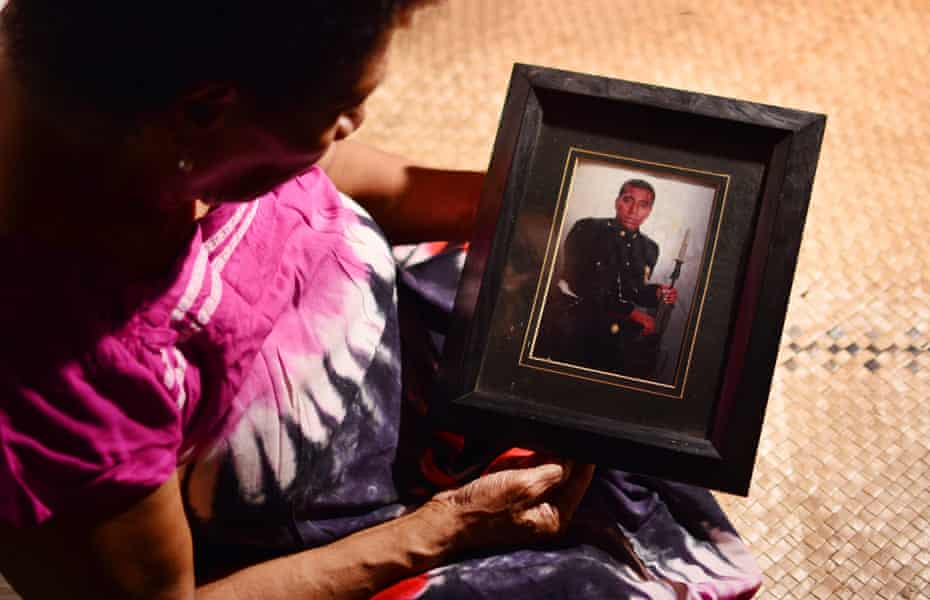 73 year old Nainasa Roiroi (also known as Nainasa Valetabua) holding a framed photograph of her son Taitusi Ratucaucau at her home in Lami, Fiji. Picture: Jovesa Naisua/The Guardian