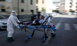 Medical staff in protective clothes carry a patient down a street in Naples.