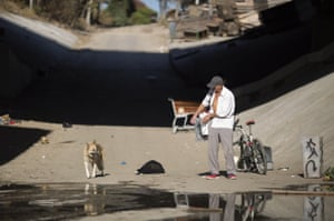 A homeless dog arrives to drink from the river alongside Lopez.
