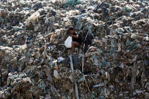 Phnom Penh, Cambodia: A boy working at a refuse site retrieves metal and wire for recycling