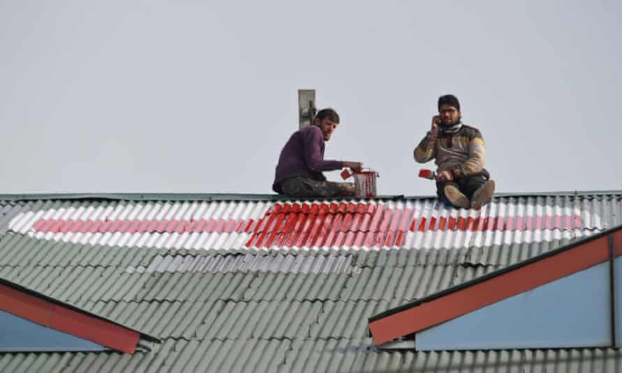 Workers paint a red cross on the rooftop of a hospital in Srinagar.