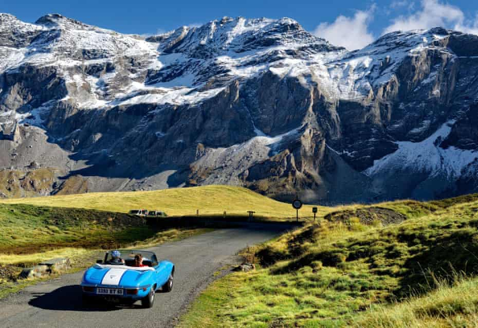 Car driving amid the snow-capped Pyrenees in France.