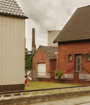 Neurath, Germany: Rhineland is home to some of Europe's biggest coal complexes. Here, a cooling tower peeps out from between residential houses near Neurath. Nearby plants Neurath and Niederaußem are two of Europe's single biggest CO2 emitters