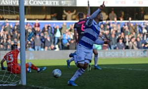 QPR's Nahki Wells wheels away in celebration after opening the scoring whilst the Leeds players claim for handball.