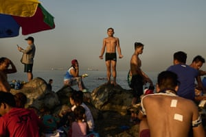 Beseco, Philippines: families flock to a makeshift beach in the polluted waters of Manila bay, to escape the summer heat. The beach in the slum village was opened to the public as the country enters the summer season. As coronavirus restrictions are still in place, the beach is only open for two hours in the early morning every Sunday