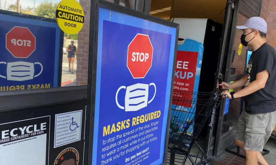 A man wearing a mask walks into a grocery store in Los Angeles.