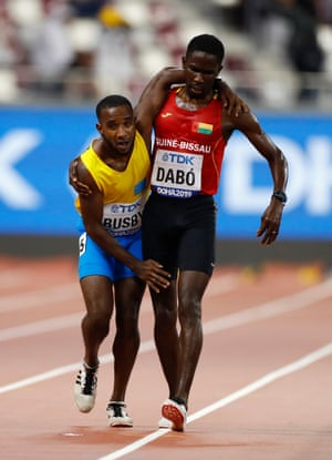Guinea-Bissau's Braima Suncar Dabo helps Aruba's Jonathan Busby to the finish in the men's 5000m heats during the World Athletics Championships at the Khalifa Stadium in Doha, Qatar.
