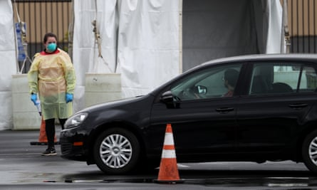 A medical worker guides a car that is going through a coronavirus drive-thru test clinic in San Mateo.