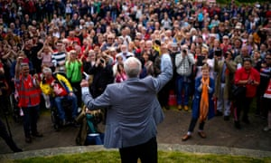 Jeremy Corbyn, with his back to the camera, addresses a rally in Bootle, Merseyside.