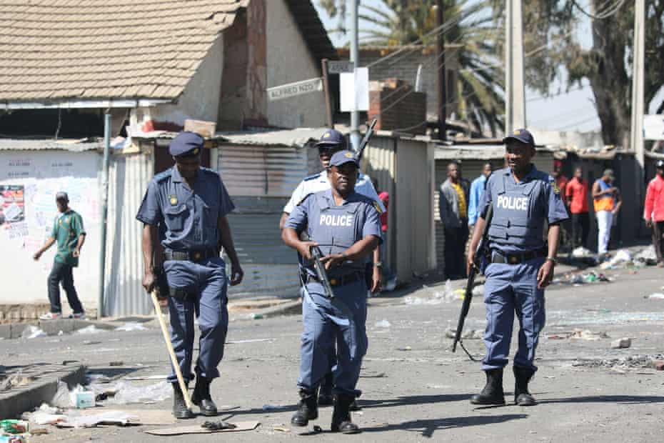 Police patrol the streets after overnight unrest and looting in the Alexandra township in Johannesburg