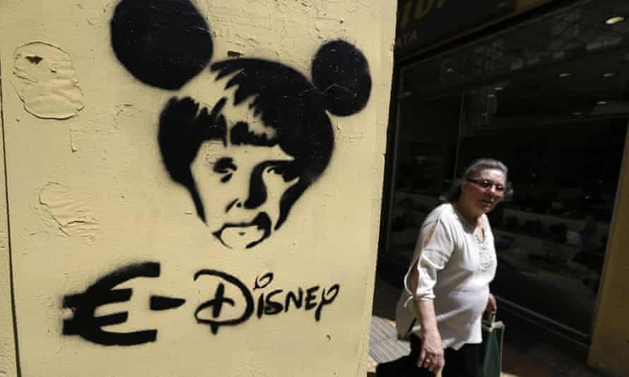 A pedestrian passes a stencil graffiti mocking Angela Merkel in Athens