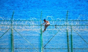 A migrant climbs a fence fortified with razor wire