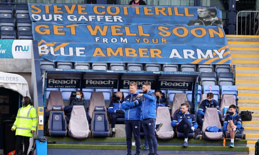 Aaron Wilbraham and David Longwell on the touchline in front of a banner in support of Steve Cotterill, who has spent 49 days in hospital.