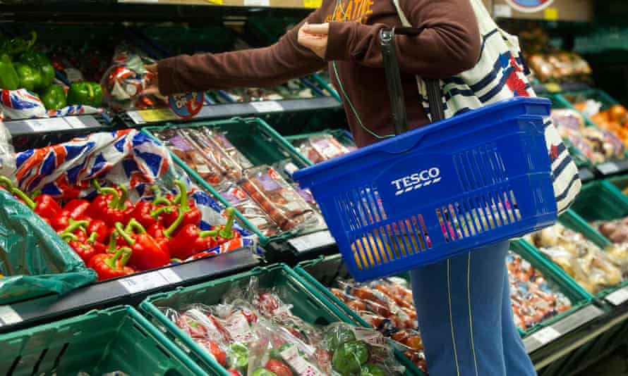A Tesco shopper selects a pack of bell peppers