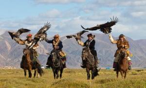 Four Kazakh eagle hunters riding