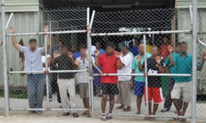 Asylum seekers housed in Delta compound look on from behind a fence