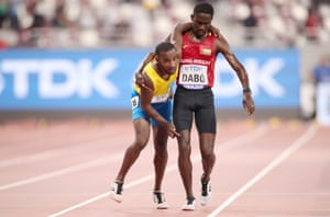 Braima Suncar Dabo of Guinea-Bissau helps Aruba's Jonathan Busby cross the finish line in the men's 5000m heats during the World Athletics Championships in Doha.