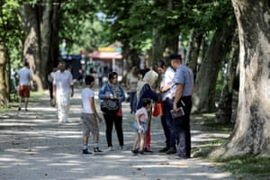 Migrants talk with a police at a park