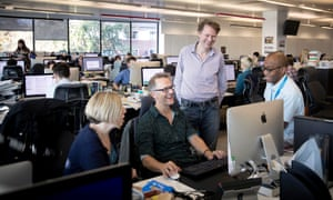 Journalist Luke Harding (centre standing) speaking with colleagues in the Guardian office.