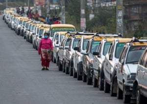 Lalitpur, Nepal. A woman walks past a line of parked taxis