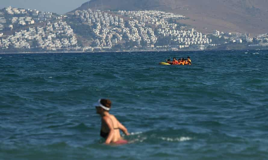 A woman wades through waves in Kos while in the background people use a dinghy to journey through Europe