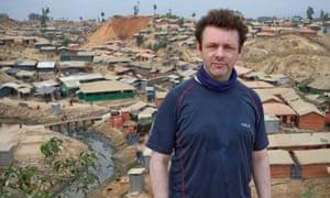 Michael Sheen on a hill overlooking a refugee camp