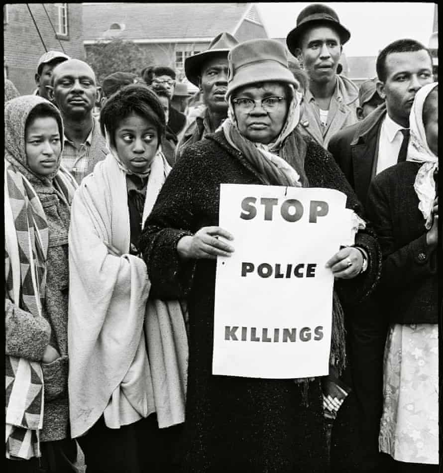 A spectator with a sign condemning police killings echoes the same grievances of today's Black Lives Matter movement.