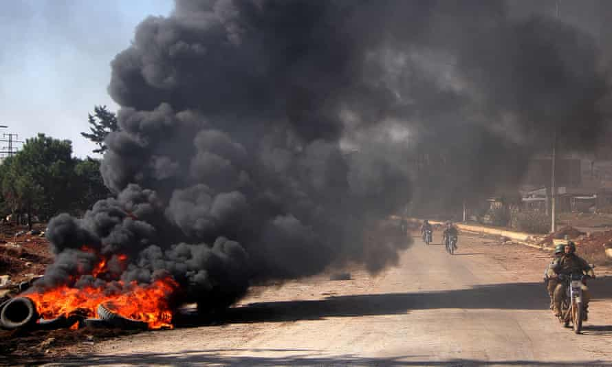 Rebel fighters drive past burning tyres at an entrance to Aleppo