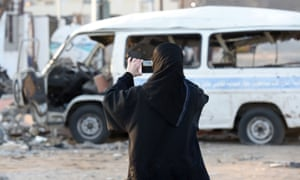 A Saudi female journalist films damage at a market at the Saudi border city of Najran in 2016