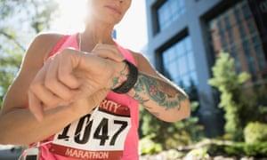 Tattooed female marathon runner checking smart watch in urban park