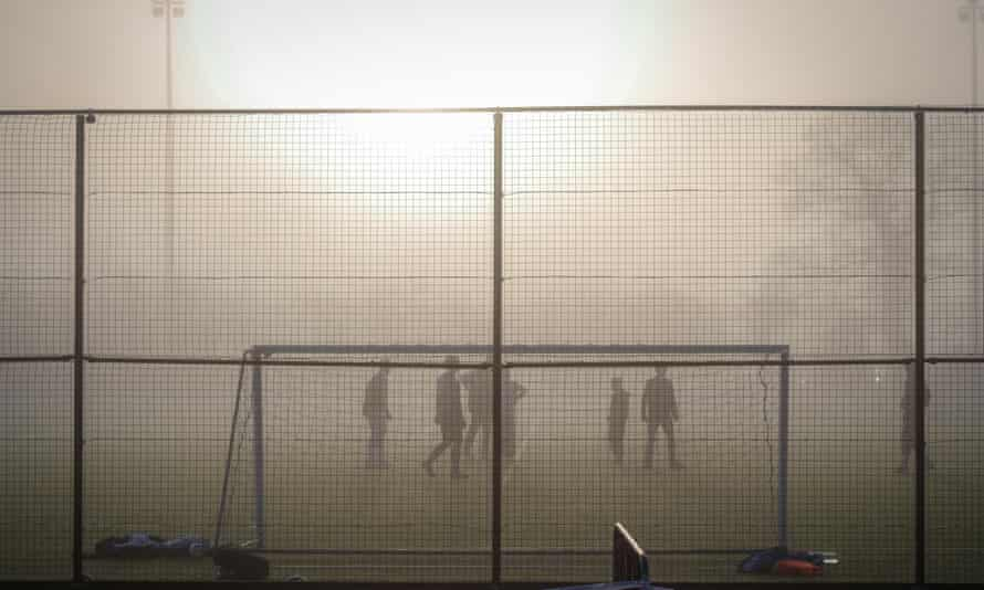 Footballers play on through tough conditions.