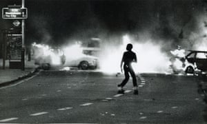A young man amid the flames of the Brixton riots of 1981