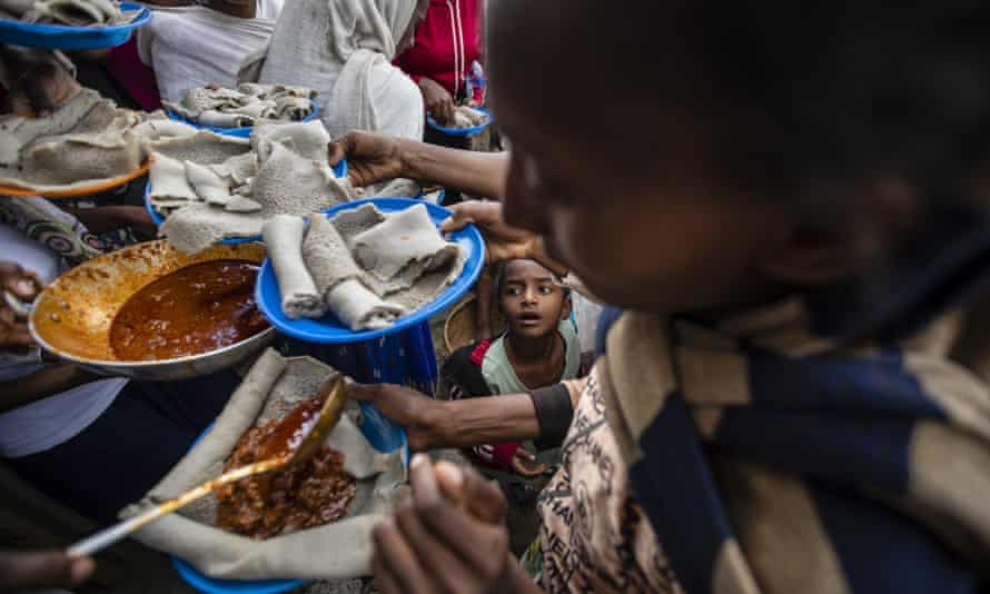 Displaced Tigrayans line up to receive food donated by local residents at a reception centre for the internally displaced in Mekele