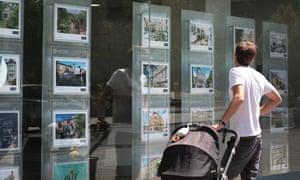 Man looking in estate agent's window