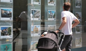 A young dad looking at houses in an estate agent's window