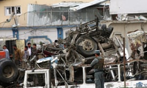 Afghan security force officers inspect the site of the suicide bombing attack.