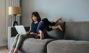 Woman sitting on sofa using laptop while child performs handstand