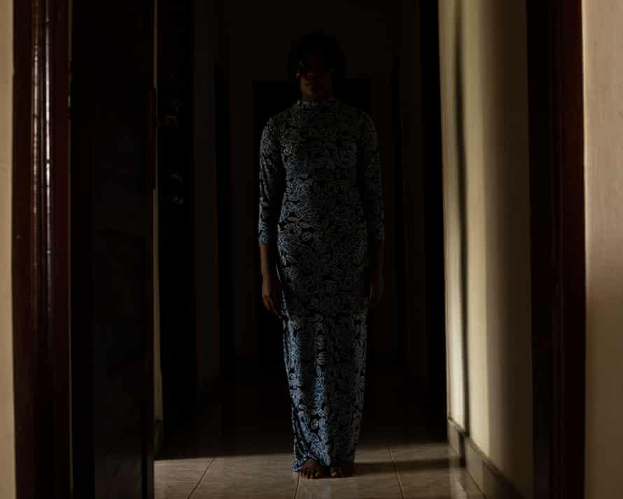 Standing in long blue patterned dress, in darkened room so her face is not seen